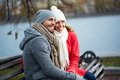 Restful couple image of affectionate young sitting on the bench in park Stock Photography