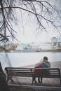 Restful couple image of affectionate young sitting on the bench in park Royalty Free Stock Photo