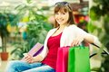 Restful customer pretty lady with colorful shopping bags sitting in trade center Royalty Free Stock Photo