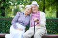Restful seniors happy sitting on bench and having rest in the park Royalty Free Stock Photo