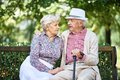 Restful seniors in smart casual sitting on bench in park and talking Royalty Free Stock Photos