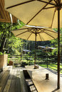 Resting area with wooden table under umbrella in garden Royalty Free Stock Images
