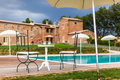 Resting a beautiful and luxurious tuscany swimming pool with parasols and chairs Stock Photos
