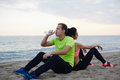 Resting couple of two runners sitting on the beach young fit having break after workout outdoors beautiful caucasian men Stock Photo