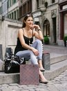 Resting after long shopping day photo of a beautiful young woman sitting and with her bags at a fountain in an old european city Royalty Free Stock Photo