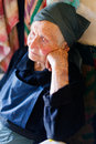 Resting old tired lady sitting and contemplating with hands holding her head Royalty Free Stock Photo