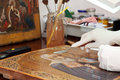 Restoration of old icon with palette knife closeup at workshop Stock Photo