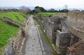 Restored ruins of the ancient city pompeii narrow paved street is recovered in middle roman has been a popular tourist destination Royalty Free Stock Image