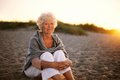 Retired caucasian lady relaxing outdoors portrait of happy old woman sitting on the beach Royalty Free Stock Photo