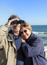 Retired couple on beach vacation with binoculars hugging happy senior enjoying themselves at a beautiful their winter or spring Stock Photo