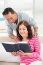 Retired couple enjoying reading home Royalty Free Stock Photos