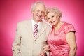 Retired couple portrait of a charming posing against pink background Royalty Free Stock Photography
