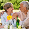 Retired couple sitting at table holding hands outdoors Royalty Free Stock Images