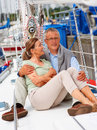Retired couple sitting together on a sailboat Royalty Free Stock Photos