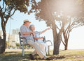 Retired couple taking a break and relaxing on a bench outdoor shot of senior sitting park with women showing something interesting Royalty Free Stock Images