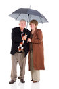Retired couple umbrella lovely under a on white background Royalty Free Stock Image