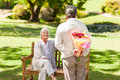 Retired man offering flowers to his wife Stock Photos