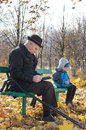 Retired man reading in the park with his grandson disabled men on crutches sitting book sitting other end bench playing on tablet Stock Image