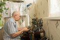 Retired man working at home on his handicrafts sitting a compact workbench in house using precision tools and small scale Stock Photography
