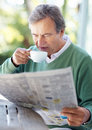 Retired old man reading newspaper in morning Stock Image