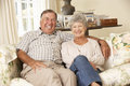 Retired senior couple sitting on sofa at home together Stock Photos