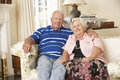 Retired senior couple sitting on sofa at home together Royalty Free Stock Images
