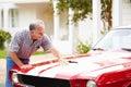 Retired senior man cleaning restored car Stock Photos