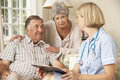 Retired Senior Man Having Health Check With Nurse At Home Royalty Free Stock Photo