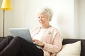 Retired senior woman working on her laptop sitting at home using Royalty Free Stock Images