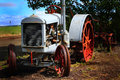 Retired tractor an old abandoned deserted mccormick deering hand crank outlives it s usefulness and sits in a field Stock Photo