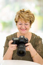 Retired woman camera smiling viewing pictures on at home Stock Image