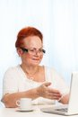 Retired woman pointing at laptop screen Royalty Free Stock Photos