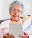 Retired woman reading a book at home and smiling Stock Images