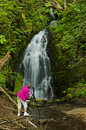 Retired woman taking pictures of a waterfall elderly from her tripod the small cascading out in the forest Stock Photo