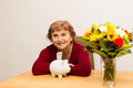 Retiree with a piggy bank sitting at table Royalty Free Stock Images