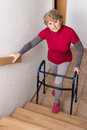 Retiree with walker standing in front of a stairway Stock Photography