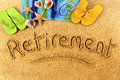 Retirement beach writing background with towel and flip flops and words written in sand Stock Photo