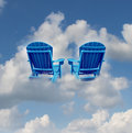 Retirement dreams and financial freedom planning symbol with two empty blue adirondack chairs floating on a cloud as a business Stock Image