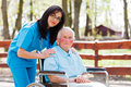 Retirement home beautiful doctor nurse in blue coat walking a kind elderly lady in wheelchair in park Royalty Free Stock Photography