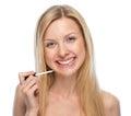 Retrato da jovem mulher de sorriso que aplica o brilho do bordo Imagens de Stock Royalty Free