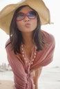 Retrato das mulheres na praia que faz a cara de beijo na câmera em um chapéu flexível do sol Fotografia de Stock