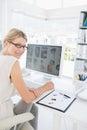 Retrato de la vista lateral de un editor de fotos de sexo femenino que trabaja en el ordenador Fotografía de archivo libre de regalías