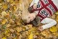 Retrato do ângulo alto da jovem mulher que encontra se nas folhas de outono no parque Imagem de Stock Royalty Free