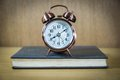 Retro alarm clock on table vintage background with and book Royalty Free Stock Images