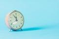 Retro alarm-clock time on blue pastel background. Royalty Free Stock Photo