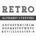 Retro alphabet vector font with distressed overlay texture serif type letters numbers and symbols on a scratched Stock Photography