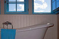 Retro bath white wood paneling and blue windows in rustical bathroom with sky in the background Stock Photography