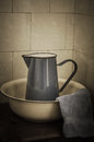 Retro bathroom jug and basin enamel wash ewer with flannel on a wooden surface tiles in background finished with weathered Royalty Free Stock Photography