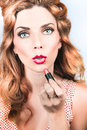 Retro beauty pin up girl applying lipstick makeup vintage fashion portrait of a cute s with amazing red hair style model Stock Images