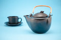 Retro black tea pot cup saucer composition blue ceramic and small in on background Stock Photo